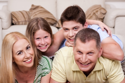 """Smiling Family Lying Together On The Floor"" by photostock"